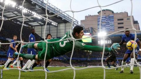 Chelsea keeper Thibaut Courtois makes a save against Leicester