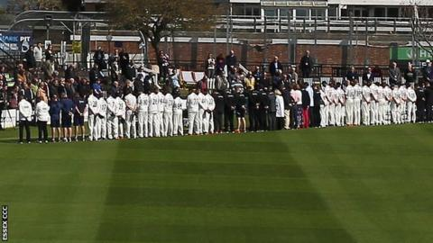The Sussex and Essex players stood to observe a minute's silence before the start of play at Hove
