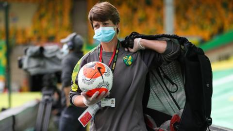 A Norwich member of staff carries balls and disinfectant