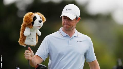 Rory McIlroy removes a club from his bag