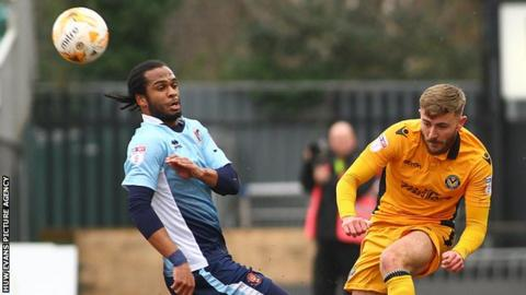 Dan Butler clears the ball under pressure from Blackpool Nathan Delfouneso