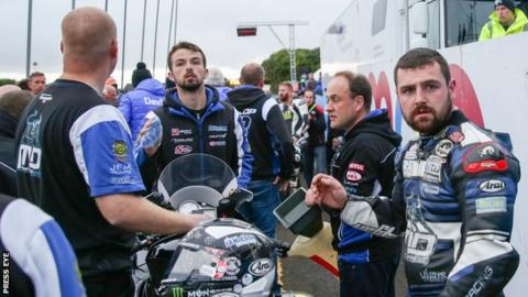 Michael Dunlop (right) waits in the paddock after the Dundrod 150 superbike race had to be red flagged
