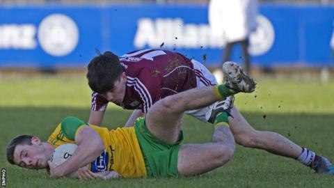 Donegal's Eoghan Ban Gallagher clings to the ball as Seán Kelly of Galway challenges