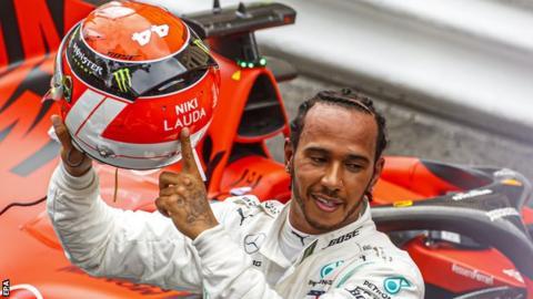 Lewis Hamilton holds up his helmet in tribute to Niki Lauda