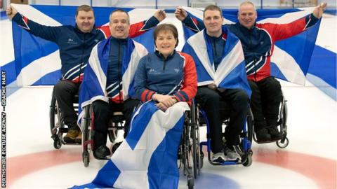 The Scottish wheelchair curling team for the World Championships holding Saltire flags