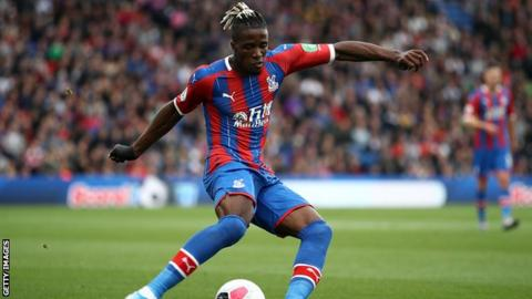 Crystal Palace forward Wilfried Zaha plays a pass during a Premier League game