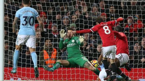 Ederson makes a save against Manchester City