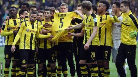 Borussia Dortmund players hold the shirt of their injured team mate Marc Bartra after winning at home on Saturday