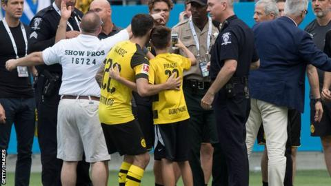 Christian Pulisic poses with a selfie with a young fan after stopping him from being dragged off the pitch by security guards