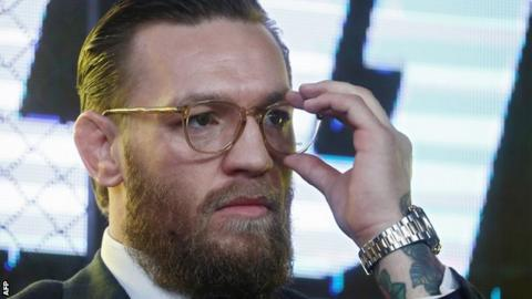 Conor McGregor touches his spectacles