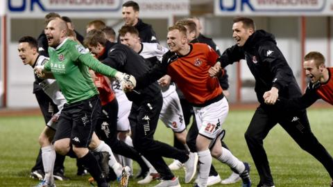Savouring success - Stephen Baxter and his players link up for a rush towards the delighted Crues support