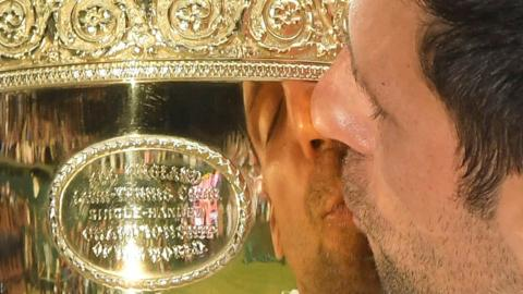 """Tennis - Wimbledon - All England Lawn Tennis and Croquet Club, London, Britain - July 14, 2019 General view of the reflection on the trophy of Serbia""""s Novak Djokovic kissing it as he celebrates winning the final against Switzerland""""s Roger Federer REUTERS/Toby Melville TPX IMAGES OF THE DAY"""