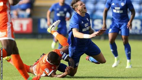 Greg Halford of Cardiff City is tackled by Abu Ogogo of Shrewsbury