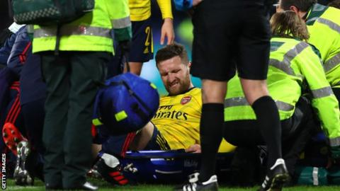 Shkodran Mustafi grimacing as he sits on a stretcher