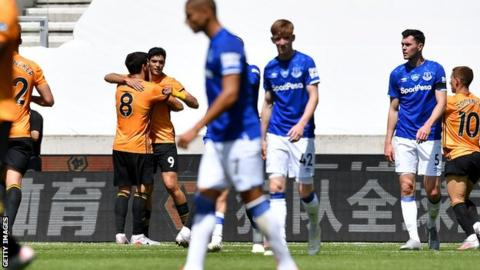 Raul Jimenez celebrates with Ruben Neves (number 8) as Everton players look despondent