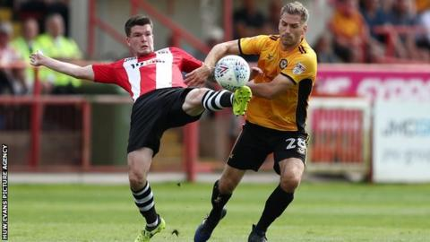 Exeter City's Liam McAlinden battles for the ball with Mickey Demetriou of Newport County