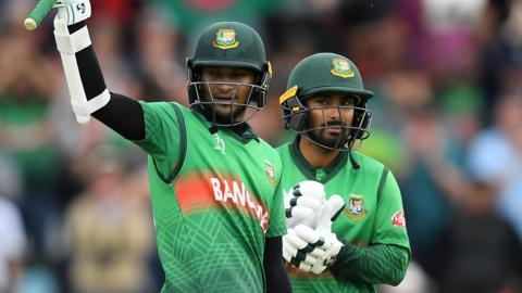 Bangladesh all-rounder Shakib Al Hasan (left) raises his bat to celebrate hitting a century against West Indies and is congratulated by team-mate Liton Das (right)