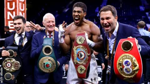 Anthony Joshua holds the belts up and celebrates with his team after beating Andy Ruiz Jr in December