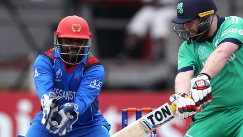 Afghanistan wicketkeeper Mohammad Shahzad closes in as Paul Stirling plays a shot