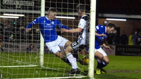 Queen of the South's Kevin Holt clears an effort from Ayr's Mark McKenzie