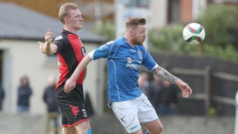 Steven Gordon and Ryan Harpur keep their eyes on the ball during Glentoran's win over Dungannon Swifts