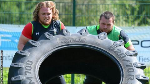 Kristian Dacey and Ken Owens grapple with a huge tyre during Wales training in Switzerland