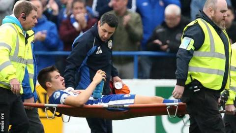 Brad Lyons is stretchered off after sustaining his injuries in the league win over Linfield