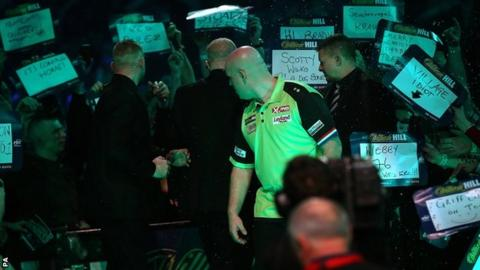 Michael van Gerwen turns to face the crowd after he was soaked in beer at Alexandra Palace