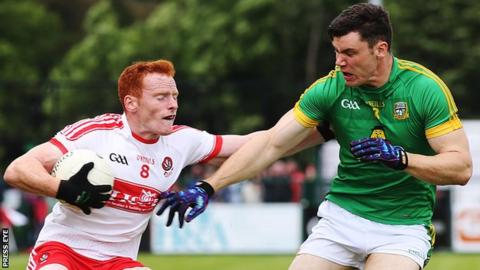 Derry's Conor McAtamney is challenged by Harry Rooney of Meath