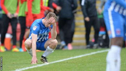 Hartlepool's Rhys Oates sits dejected on the turf