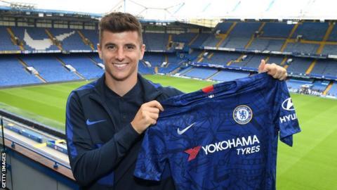 Mason Mount holding up a Chelsea shirt