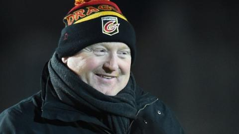 Bernard Jackman is wrapped up against the cold and smiling before Dragons' match with Newcastle Falcons
