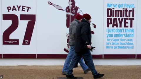 West Ham United fans outside London Stadium near Dimitri Payet signage