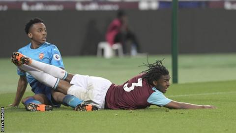 Vashon Neufville of West Ham United and Joe Willock of Arsenal both land on the ground during the Premier League 2 match between West Ham United and Arsenal at London Stadium on April 20, 2018