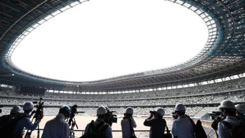 Media assess construction work at the Tokyo National Stadium earlier in July