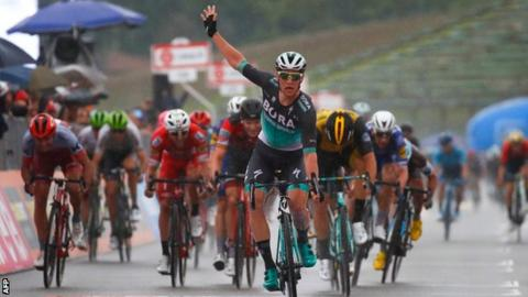 Sam Bennett raises a hand in celebration as he wins at Imola