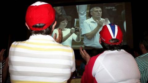 Marie Valova watching her friends - Kvitova's parents Jiri and Pavla - on the big screen while she is watching the Wimbledon final