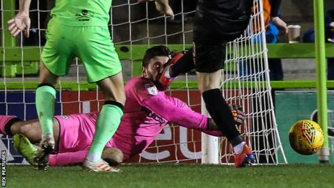 Forest Green Rovers goalkeeper James Montgomery takes a boot to the face