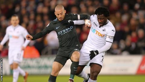 Wilfried Bony of Swansea City takes on David Silva of Manchester City