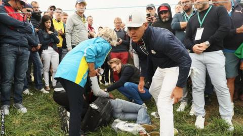 Brooks Koepka attends to the injured woman