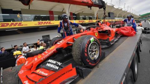 Sebastian Vettel's damaged car is taken back to the garage