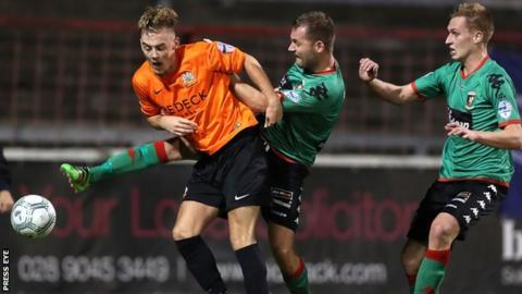 Glentoran midfielder Ciaran Caldwell gets to the ball ahead of Glenavon's Joel Cooper