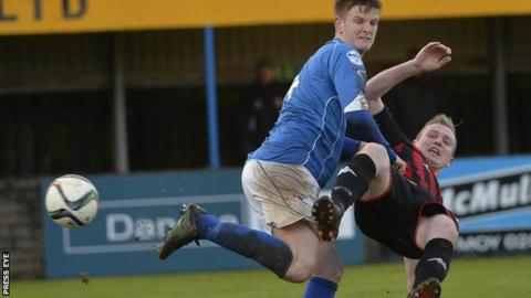Dungannon's Dougie Wilson gets in a tangle with Crusaders striker Jordan Owens