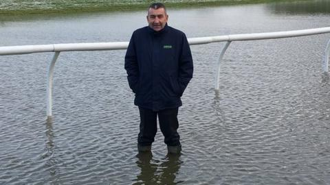 Chepstow Racecourse chief executive Phil Bell stands knee deep in water at the course on 27 December, 2017