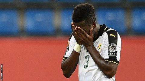 Ghana captain Asamoah Gyan holds his head in his hands as he leaves the pitch because of an injury