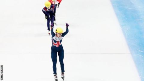 Elise Christie raises her arms aloft after winning the 1000m in Dordrecht
