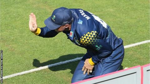 Glamorgan's Shaun Marsh signals for assistance after hurting himself while fielding