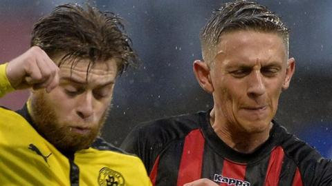 Cliftonville's James Knowles in action against Matthew Snoddy of Crusaders
