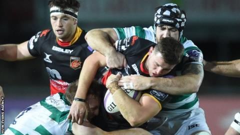 Elliot Dee of Dragons is tackled by Ben Sowrey and Gary Graham