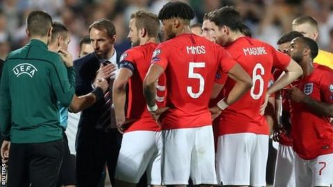 England players speak to Uefa officials during the game in Sofia
